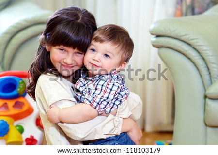 beautiful little brother and sister embracing in home interior