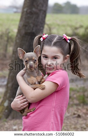 Beautiful little brown eyed brunette girl holding a little chihuahua outdoors with natural green background
