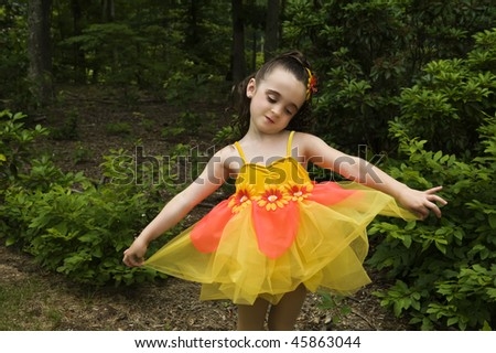 beautiful little brown-eyed, brunette girl with  make-up wearing a costume