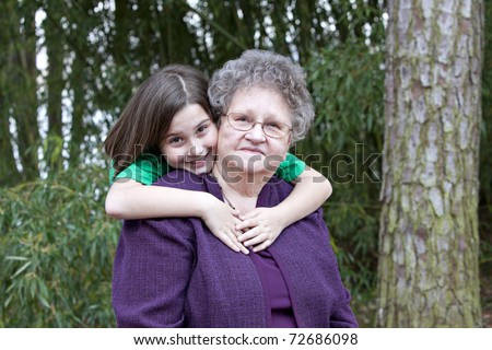 Beautiful little brunette girl hugging her Great Grandmother in outdoor wooded setting