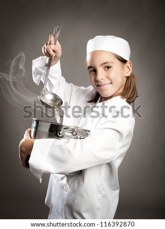 beautiful little chef cooking on gray background - stock photo