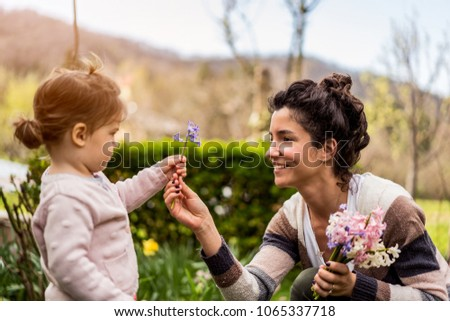Beautiful little child baby girl giving flower to gorgeous mom #1065337718