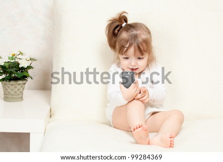 beautiful little child holds a cell phone