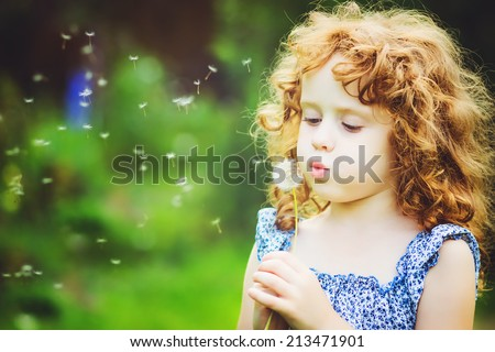 Beautiful little curly girl blowing dandelion horizontal shot