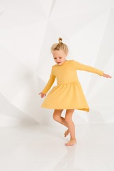 Beautiful little fashion model on white studio background. Portrait of cute girl posing in studio