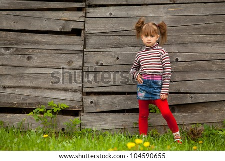 Beautiful little five-year girl posing for the camera outdoor near wooden wall