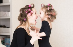 Beautiful little girl and woman, has crying fun face, long hair, curlers roller, black underwear combies dress. Family portrait. Creative concept. Close up. Mom and daughter, relationship love