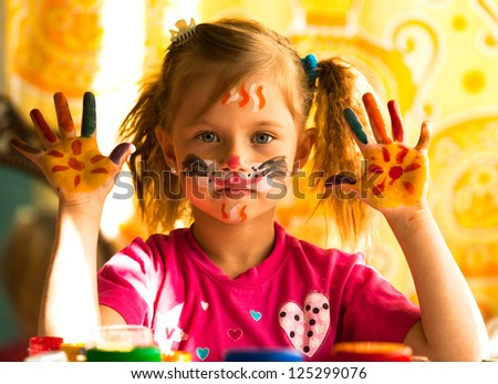 Beautiful little girl artist with paint of face - stock photo