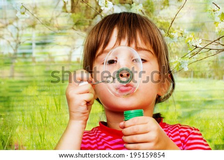 Beautiful little  girl blowing soap bubbles indoor