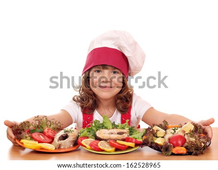 beautiful little girl cook with prepared salmon seafood