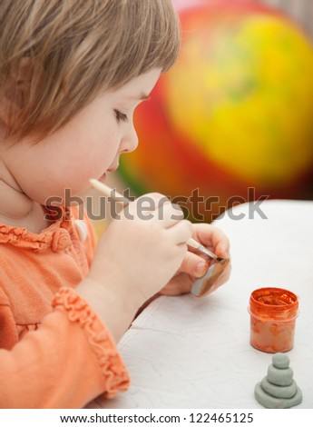 Beautiful little girl covers clay toys with drawings