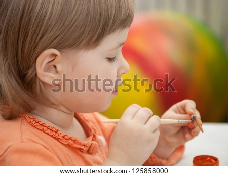 Beautiful little girl covers with drawings clay toys - stock photo