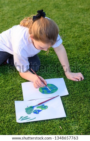 Beautiful little girl drawing with acrylic color a picture of earth globe. Child painting with brush and color a picture of earth. Earth day, plastic free and zero waste concept.