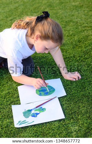 Beautiful little girl drawing with acrylic paint a picture of earth globe. Child painting with brush and color a picture of earth.Earth day, plastic free and zero waste concept.