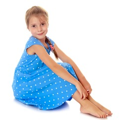 Beautiful little girl dressed in blue polka-dot dress , sitting barefoot.Isolated on white.