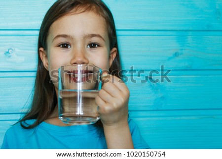 Beautiful little girl drinks clean water from a transparent glass on a blue background #1020150754