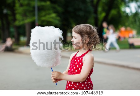 Beautiful little girl eating cotton candy in the street