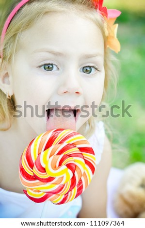 Beautiful little girl eating lollipop