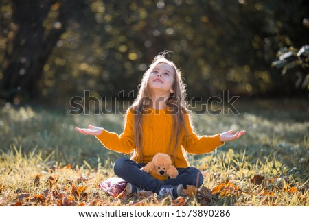Beautiful little girl, has happy fun face, long hair, enjoy and playing autumn nature, closed in ginger color jumper. Child portrait. Kids fashion style. Beauty people.