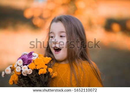 Beautiful little girl, has happy smiling face, brown eyes, long hair, enjoy autumn nature, holding bouquet of flowers, closed in ginger color jumper. Child portrait. Kids fashion style. Beauty people.
