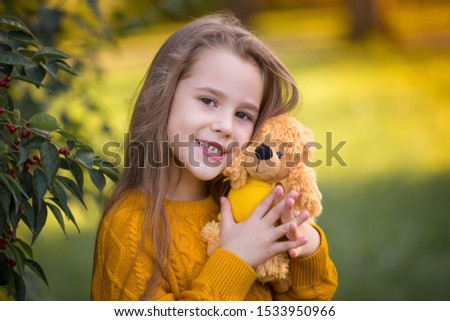 Beautiful little girl, has happy smiling face, long hair, enjoy autumn nature, playing soft toy dog , closed in ginger color jumper. Child portrait. Kids fashion style. Beauty people.