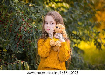 Beautiful little girl, has sad face, long hair, enjoy autumn nature, playing soft toy dog , closed in ginger color jumper. Child portrait. Kids fashion style. Beauty people.