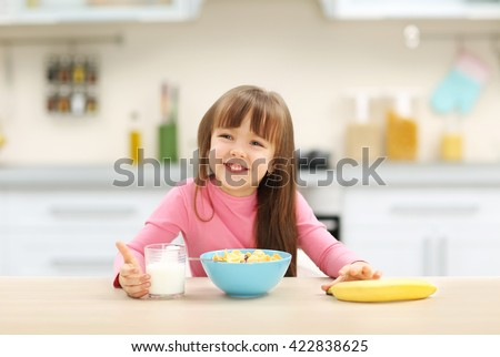 Beautiful little girl having breakfast with cereal, milk and banana in kitchen