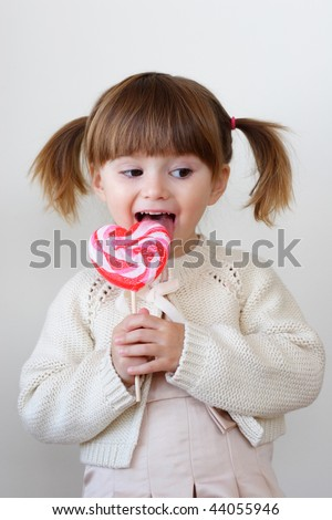Beautiful little girl holding a big heart shaped lollipop