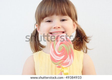 Beautiful little girl holding a big round swirl lollipop - stock photo