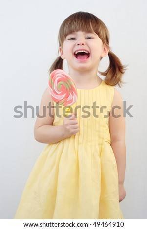 Beautiful little girl holding a big round swirl lollipop