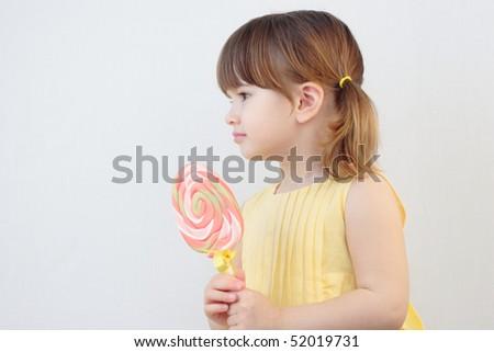 Beautiful little girl holding a big round swirl lollipop