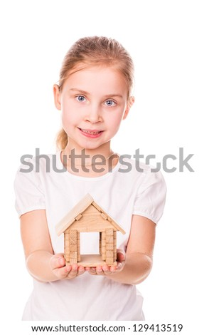 Beautiful little girl holding a toy model house isolated on white.  Buying a house concept.