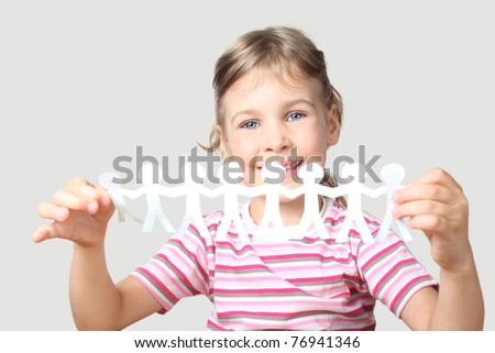 beautiful little girl holding garland of paper little people isolated on gray