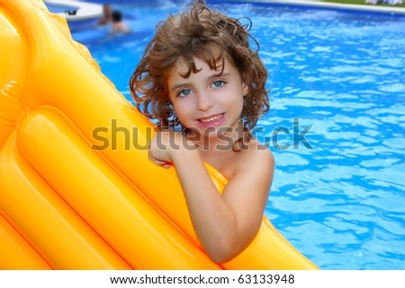 Beautiful little girl holding yellow pool float smiling over blue water
