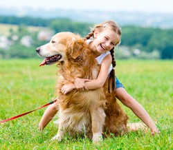 Beautiful Little girl hugging retriever in the summer park