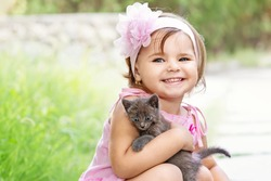 Beautiful little girl in a pink dress and pink headband  holding gray kitten and smiling.
