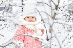 beautiful little girl in a pink fur coat and a knitted hat among the snow-covered trees. winter and christmas concept