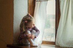 beautiful little girl in a simple dress sits on a wooden window of an old village house. quarantine regime in European countries in connection with coronavirus Covid-19