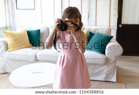 Beautiful little girl in casual pink dress is taking a photo using a camera polaroid at her home #1104388856