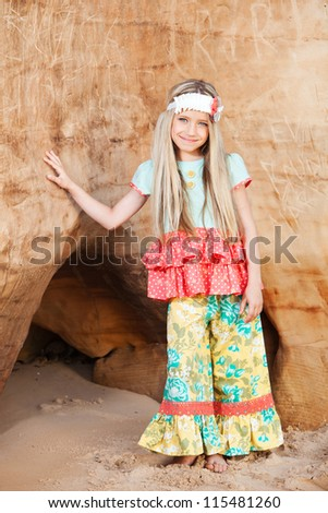 Beautiful, little girl in colorful clothing standing at the cliff with beer.