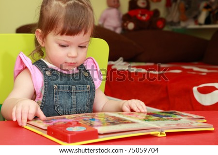 beautiful little girl in denim jumpsuit and pink shirt seats on yellow chair and reads book