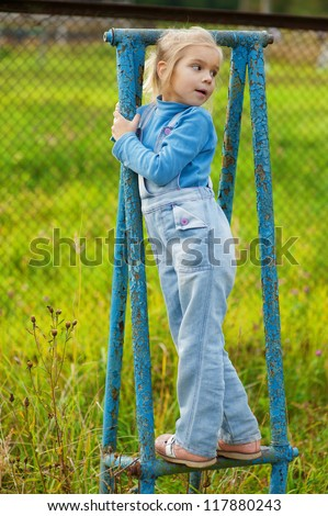 Beautiful little girl in denim suit on rusty blue gymnastic apparatus.