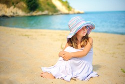 beautiful little girl in dress and beach hat sits on the beach and looks at the sea