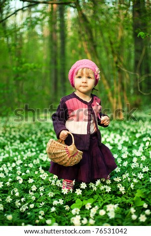 beautiful little girl in forest on flowers field