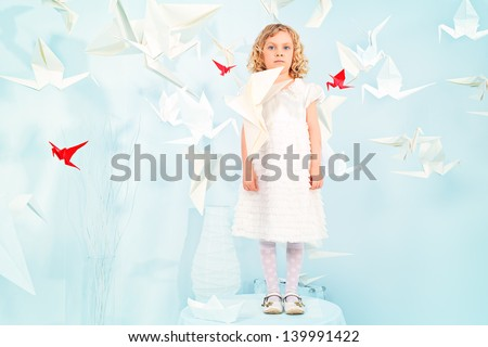 Beautiful little girl in her dream world surrounded with paper birds.