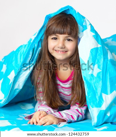beautiful little girl in pajamas lying in bed under a blue blanket