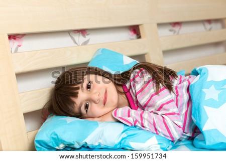 beautiful little girl in pajamas sleep in bed under a blue blanket