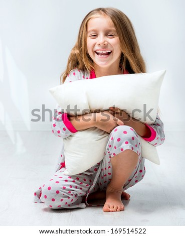 beautiful little girl in pajamas with a pillow in his hands