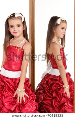Beautiful little girl in red evening dress in front of mirror on white background