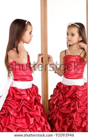 Beautiful little girl in red evening dress in front of mirror on white background - stock photo